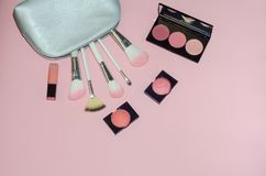 Woman cosmetic bag, make up beauty products on pink background. Makeup brushes, pink lipstick and rouge palettes. Decorative cosme. Tics. Top view, flatlay Royalty Free Stock Photography