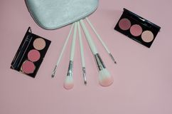 Woman cosmetic bag, make up beauty products on pink background. Makeup brushes and rouge palettes. Decorative cosmetics. Top view,. Flatlay. Copyplace, place Stock Images