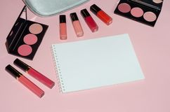 Woman cosmetic bag, make up beauty products on pink background, notebook. Red and pink lipstick. Makeup brushes and rouge palettes. Decorative cosmetics. Top Stock Photography