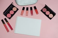 Woman cosmetic bag, make up beauty products on pink background, notebook. Red and pink lipstick. Makeup brushes and rouge palettes. Decorative cosmetics. Top stock photos