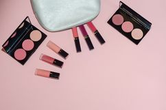 Woman cosmetic bag, make up beauty products on pink background. Pink lipsticks and rouge palettes. Decorative cosmetics. Top view,. Flatlay. Copyplace, place Royalty Free Stock Photo