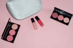 Woman cosmetic bag, make up beauty products on pink background. Red and pink lipstick. Makeup brushes and rouge palettes. Decorati. Ve cosmetics. Top view Royalty Free Stock Image