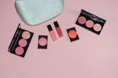 Woman cosmetic bag, make up beauty products on pink background. Red and pink lipstick. Makeup brushes and rouge palettes. Decorati. Ve cosmetics. Top view Royalty Free Stock Photos