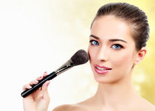 Woman with cosmetic brush Stock Photography