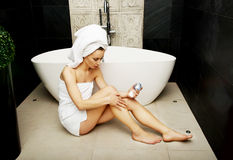 Woman with cosmetic cream in bathroom. Royalty Free Stock Photography