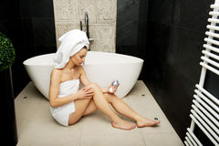 Woman with cosmetic cream in bathroom. Stock Images