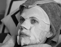 Woman with cosmetic mask. Black and white horizontal facial portrait of a woman relaxing after the application of a cosmetic skin care mask to her face Royalty Free Stock Photos