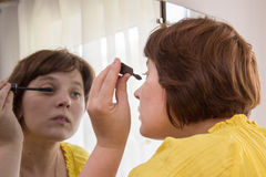 Woman in cosmetic mirror Stock Images