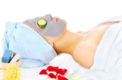 Woman on cosmetic treatmant with mask. Young woman with blue mask lying on the cosmetic table Royalty Free Stock Images