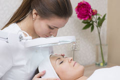 Woman and cosmetician during facial spa procedure in the beauty Stock Photos
