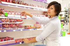 Woman   at cosmetics  shop Royalty Free Stock Images