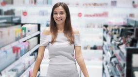 Woman in cosmetics shop thinks which product to buy, slow motion, funny video. Woman in cosmetics shop thinks which product to buy, looks at camera and smiles stock footage