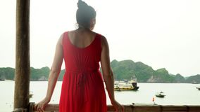 The woman costs a back to the camera. Boats at the beach of the island. A bay in Vietnam. Vietnam. The woman in a red dress in a bungalow on the bank of the stock video footage