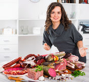Woman costs near table on which sausages and smoked meat Stock Images