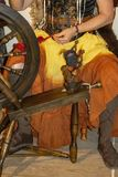 Woman in costume spins thread on an old fashioned spinning wheel - close up stock photo