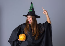 Woman in costume of witch holding a pumpkin Royalty Free Stock Images