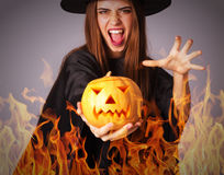 Woman in costume of witch holding a pumpkin in fire Stock Photo