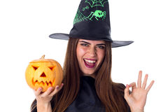 Woman in costume of witch holding a pumpkin and showing OKAY Royalty Free Stock Image