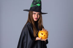 Woman in costume of witch holding a pumpkin Stock Image
