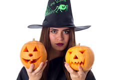 Woman in costume of witch holding two pumpkins Stock Photo