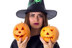 Woman in costume of witch holding two pumpkins Royalty Free Stock Image