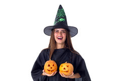 Woman in costume of witch holding two pumpkins Royalty Free Stock Photo