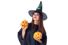 Woman in costume of witch holding two pumpkins Stock Image