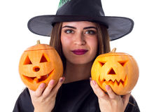 Woman in costume of witch holding two pumpkins Royalty Free Stock Images
