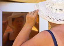 The woman at the cottage adjusts her headdress,looking at her reflection Stock Photo
