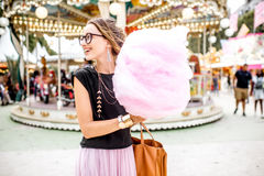 Woman with cotton candy at the amusement park. Young woman standing with pink cotton candy outdoors in front of the carrousel at the amusement park Royalty Free Stock Images