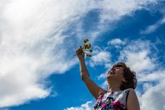 A woman in a cotton dress holds dandelions and laughs stock photo
