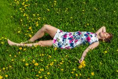 A woman in a cotton dress lies on the green grass with dandelions royalty free stock photos
