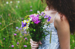 Woman in cotton dress with bunch of summer flowers in the meadow stock photos
