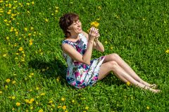 A woman in a cotton dress sits on the green grass with dandelions stock image