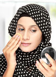 Woman with cotton pad applying face powder Stock Photos