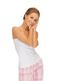 Woman in cotton pajamas making sleeping gesture Royalty Free Stock Photos