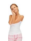 Woman in cotton pajamas making sleeping gesture Stock Photos