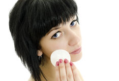 Woman with cotton swab cleaning her face. Royalty Free Stock Images
