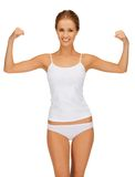 Woman in cotton undrewear flexing her biceps Royalty Free Stock Images