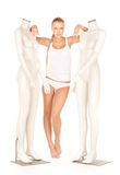 Woman in cotton undrewear with mannequins Royalty Free Stock Images