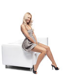 Woman on a couch. Positive blonde woman sitting on a white leather couch Royalty Free Stock Photography