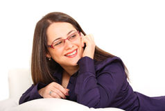 Woman on couch. Smiling woman on couch with mobile phone Royalty Free Stock Photography