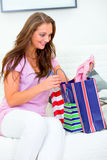 Woman on couch with bags checking purchasings Stock Images