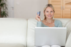Woman on the couch booking holidays online Royalty Free Stock Image