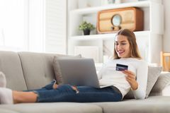 Woman on couch with credit card and laptop stock photo