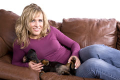 Woman on couch with dog Royalty Free Stock Photos