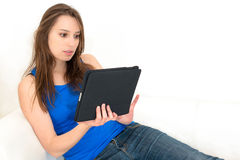 Woman on the couch with her tablet Stock Images