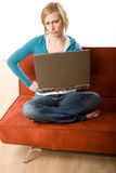 Woman on couch with laptop. A young woman sits on a couch holding a laptop computer with an annoyed and angry expression. She's against a white background Royalty Free Stock Images