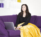 Woman on couch with laptop Royalty Free Stock Image