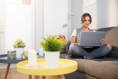 Woman on couch with laptop. Portrait of young pretty woman sitting comfortably on couch using laptop Stock Photo